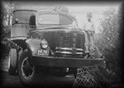 Will Logan Jr as a child with original Logan truck outside first garage.