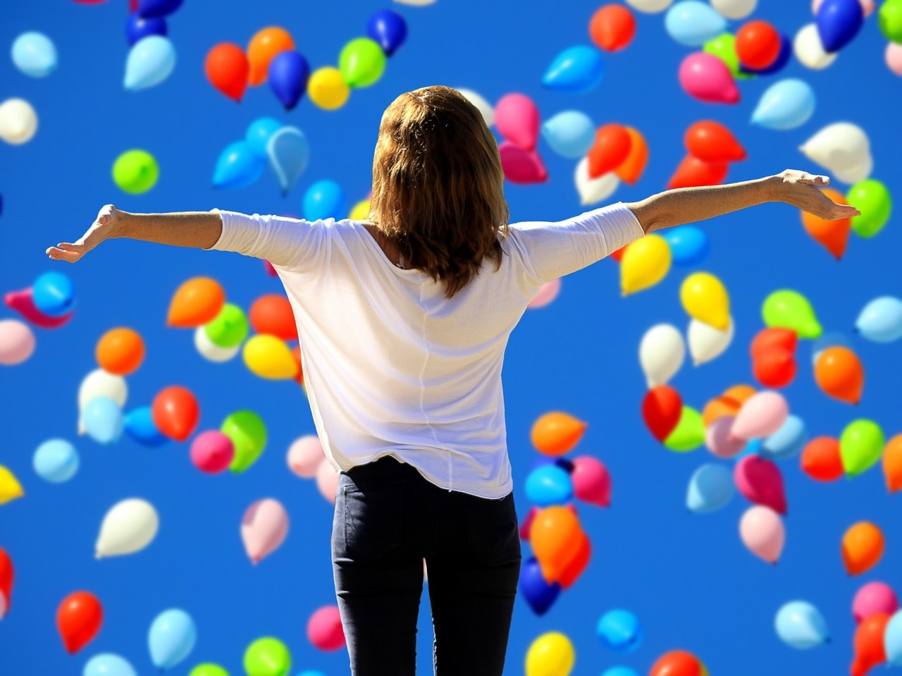 woman standing with arms outstretched before a blue sky filled with colourful balloons - ME CFS Fibromyalgia Recovery