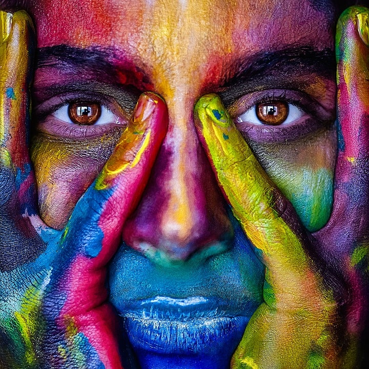 a close up of a woman's face cupped in her hands and painted in bright colours - Lifespark Coaching - Choose your values exercise