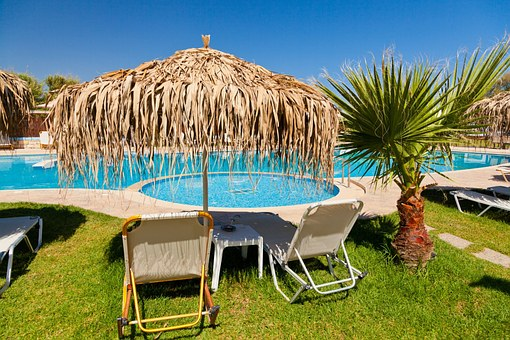 sun loungers and palm leaf umbrella next to a crystal blue swimming pool - ask for what you need when on holiday with a chronic illness