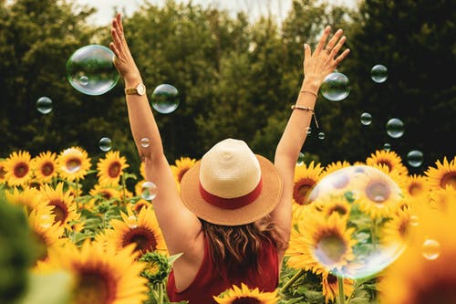 A woman in a panama hat joyfully throws her arms up as she stands in a sunflower field amongst bubbles
