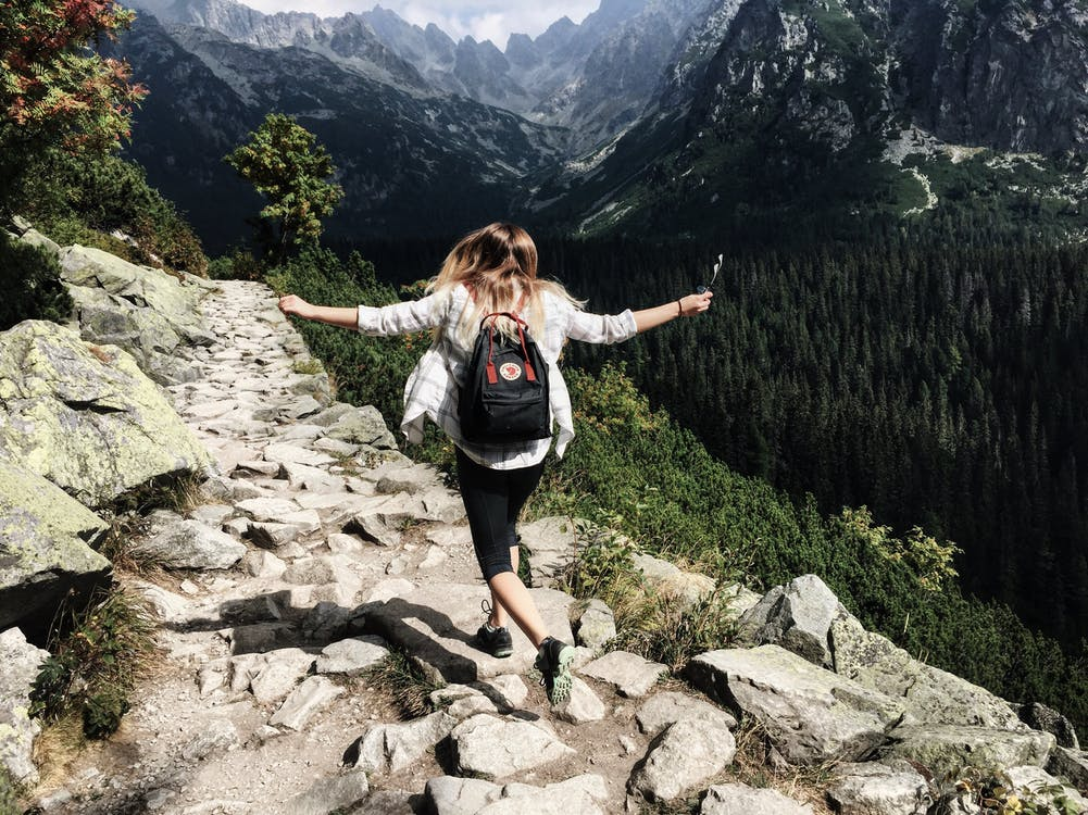 a woman with a backpack and arms outstretched runs along a stony path next to a canyon - how to set successful weight-loss goals
