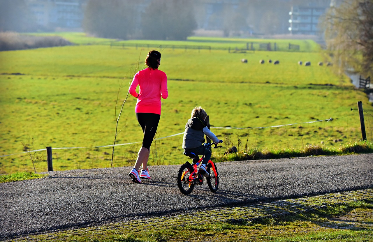 a woman in a pink top jogs along a country road with her little girl cycling alongside her - what does losing weight open up for you