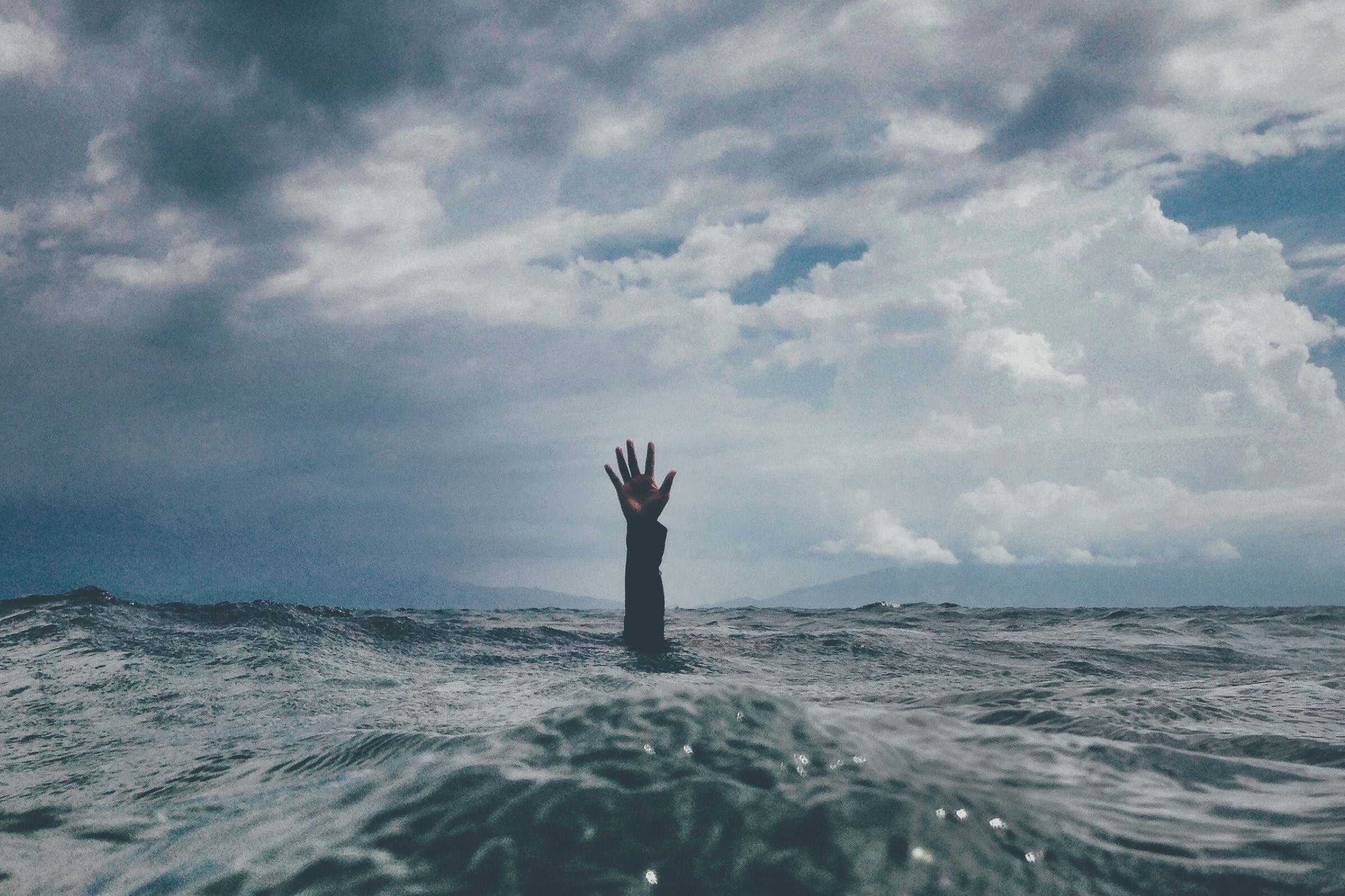 an arm reaches out of a tempestous sea, with dark clouds threatening overhead - what happens when we feel stressed