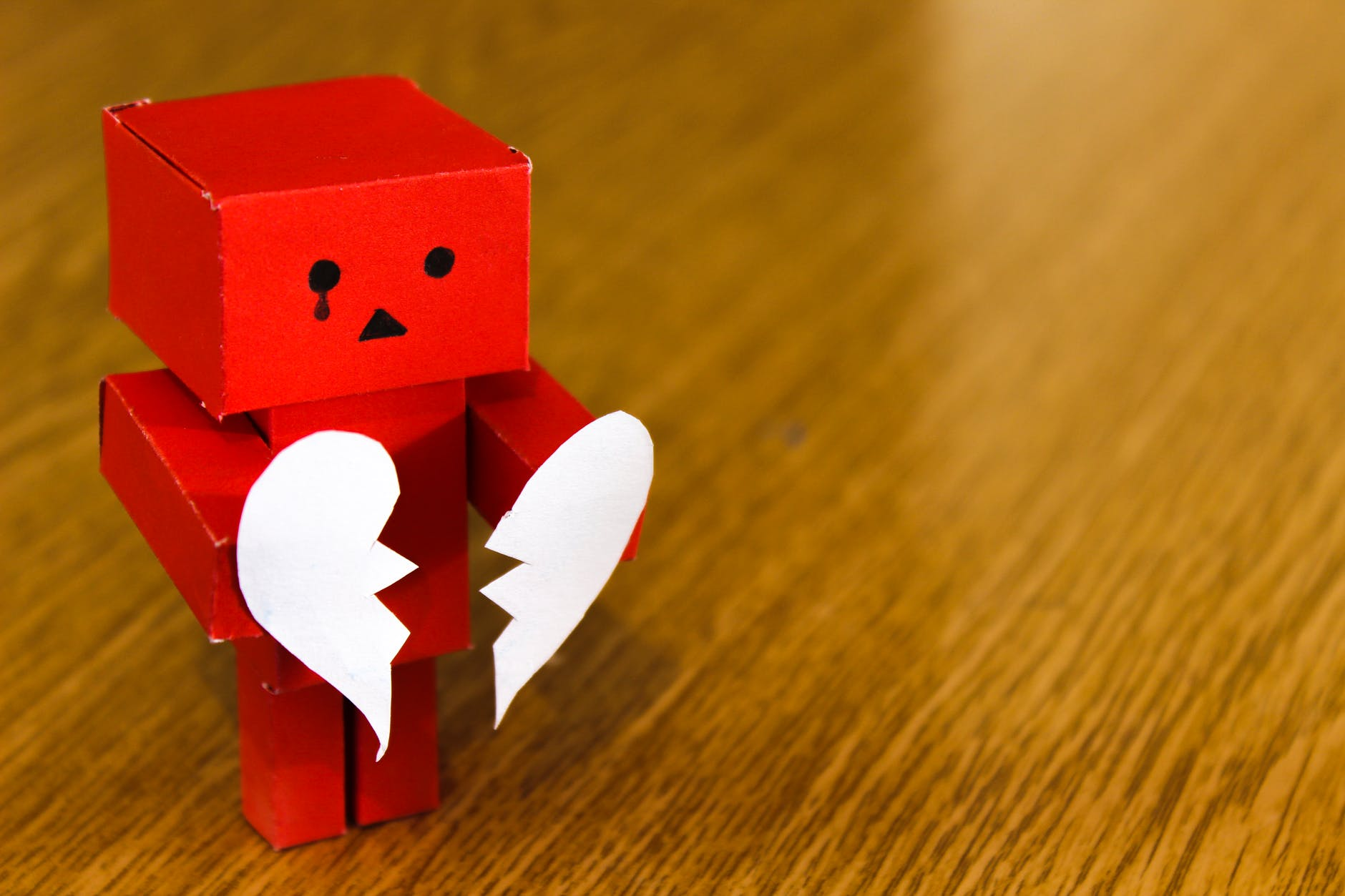 small red paper robot holding a broken paper heart - divorce causes huge stress