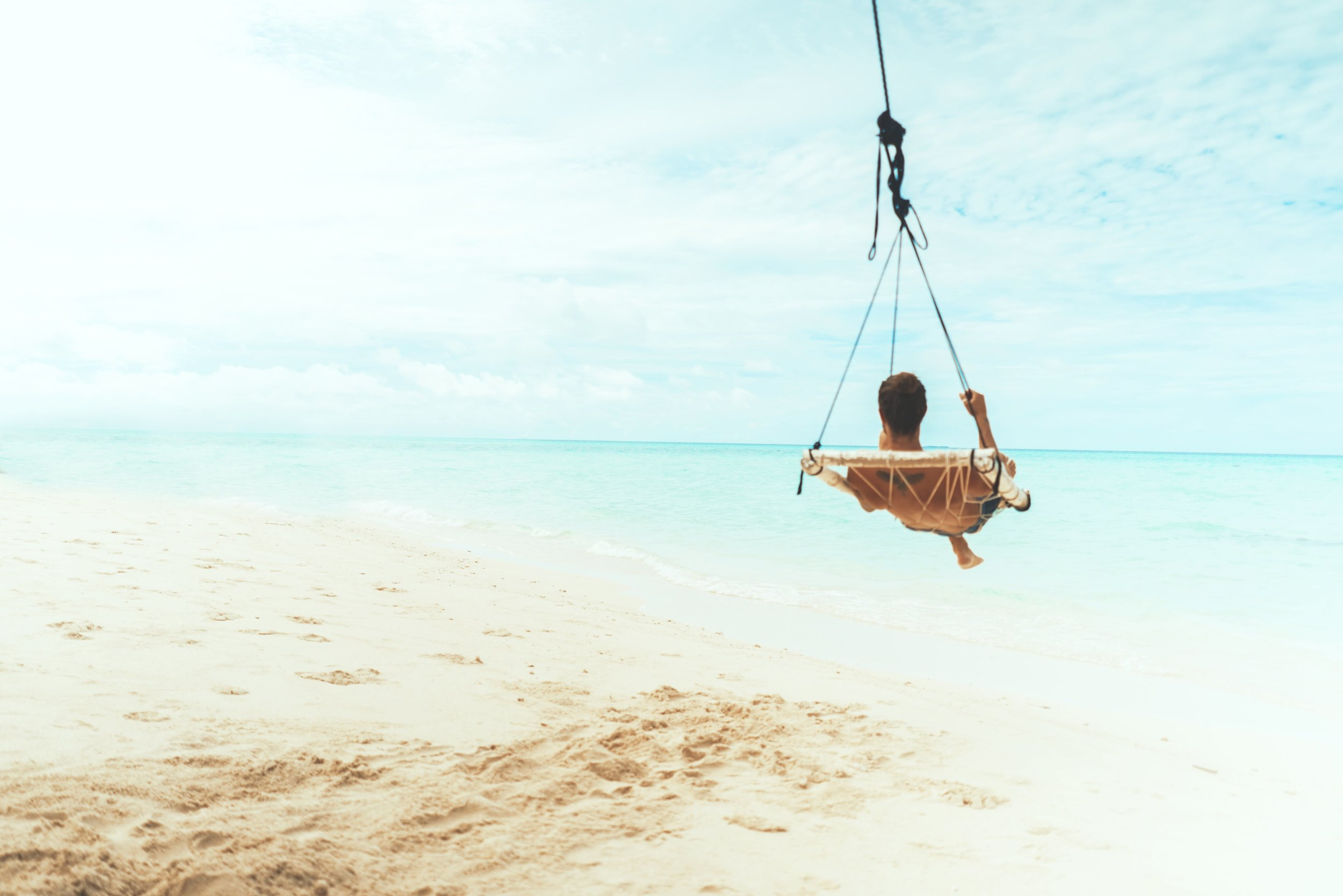a man on a swing over a white sand beach - stress resilience coaching