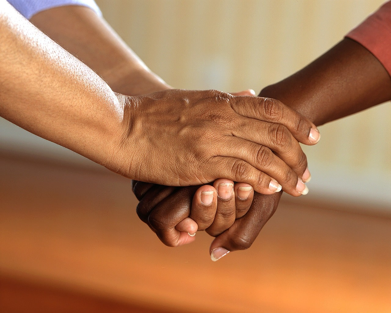 Two peoples hands are clasped together in greeting - how to start a courageous conversation
