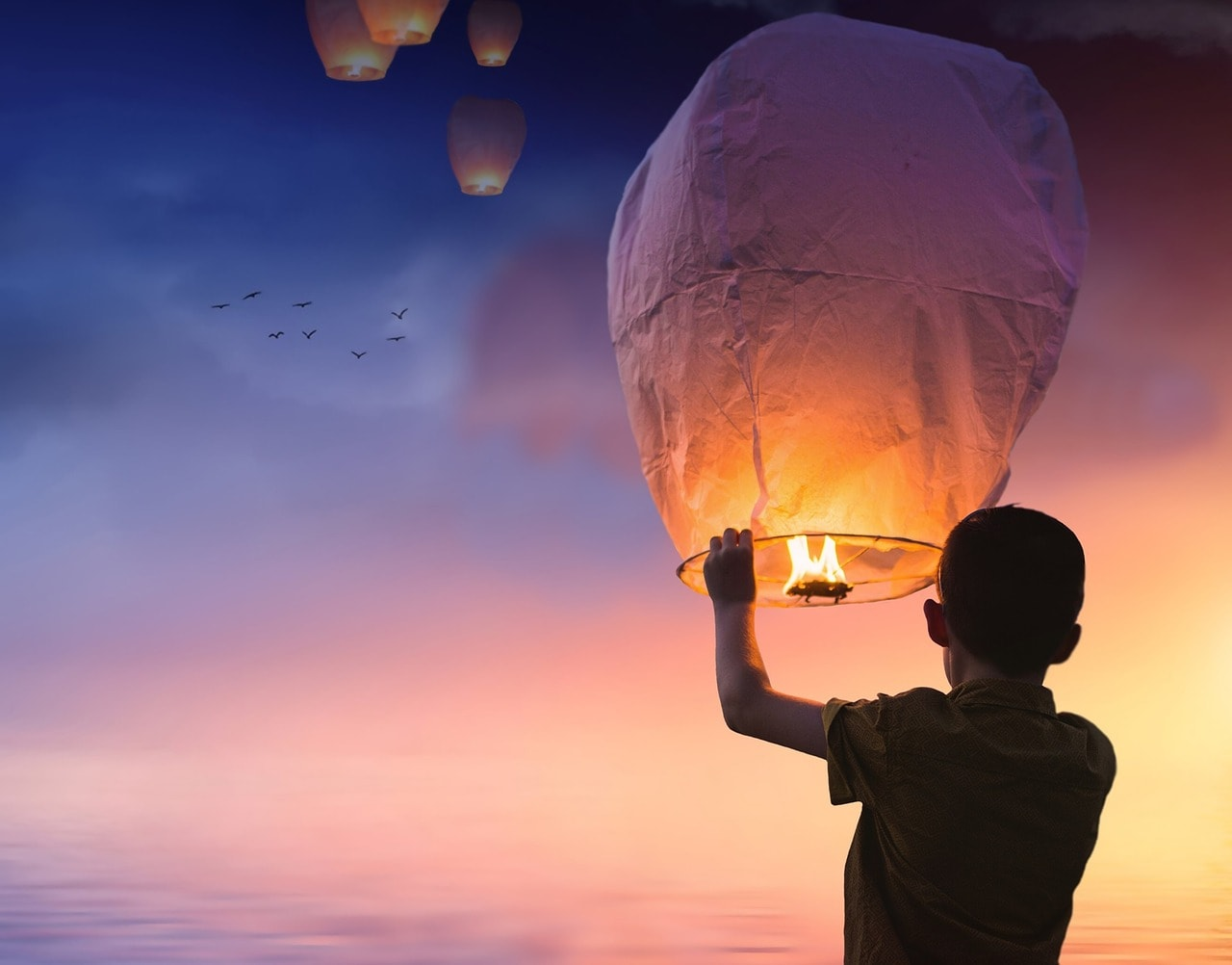 a silhouetted figure releases a chinese lantern into the sky - live your best life with life coaching