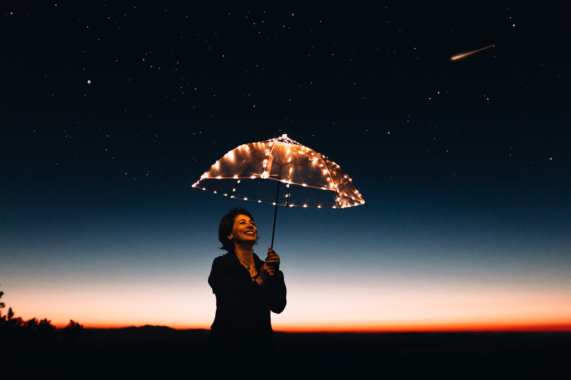 a woman holds an umbrella covered with fairy lights against a night sky - life coaching for self development and personal development - NLP