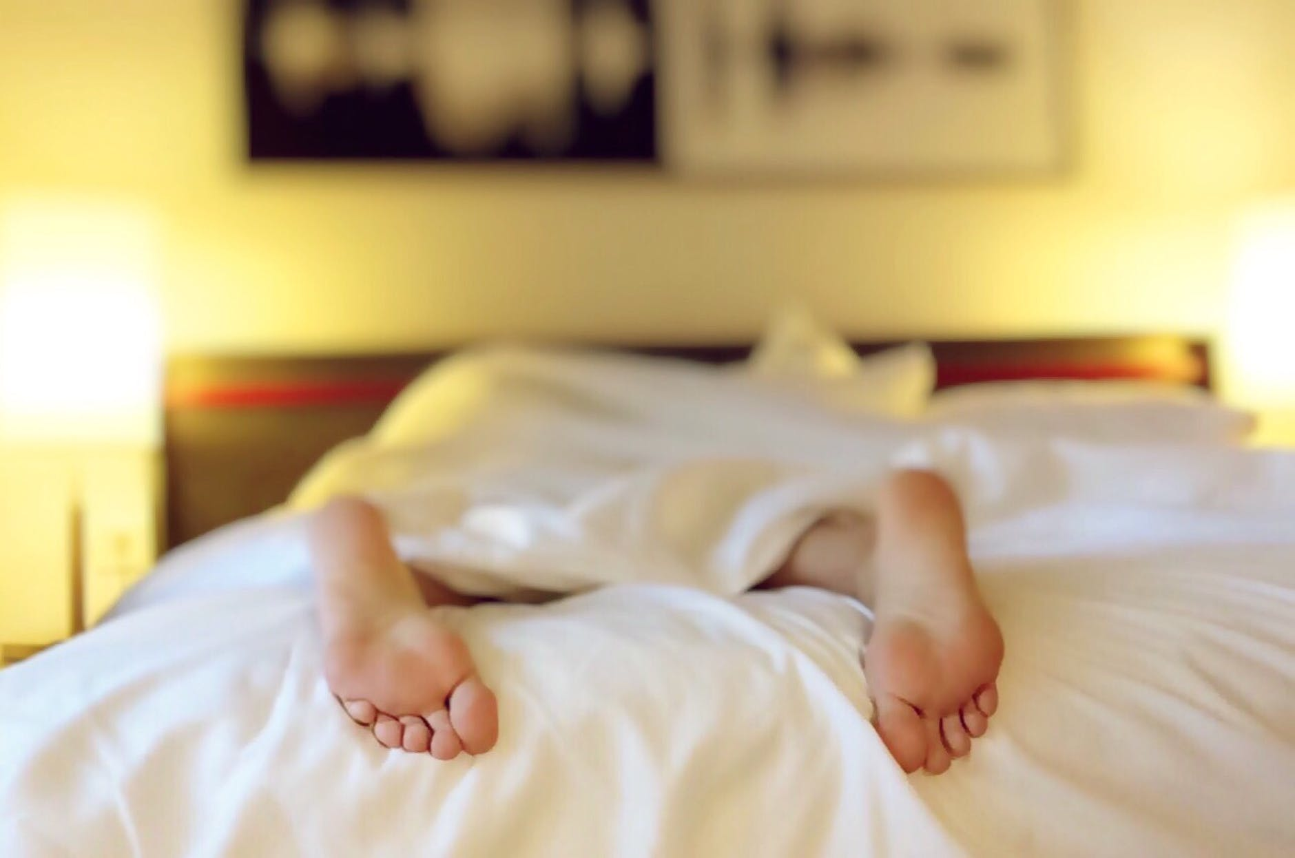 a pair of feet sticking out of the end of a bed with white bed linen - tired all the time - life coaching for optimum wellbeing