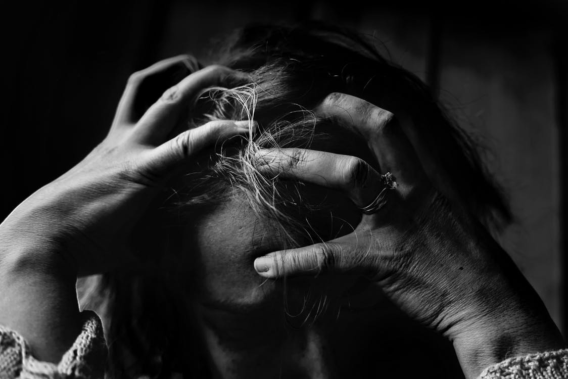 a black and white photo pf a stressed person with their head in their hands