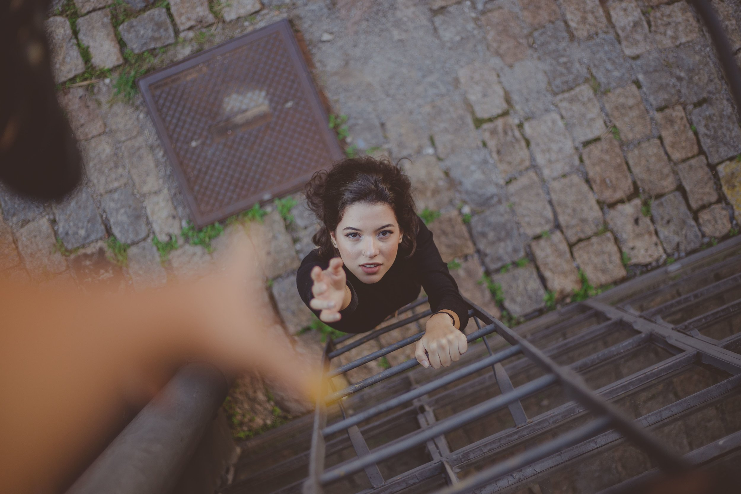 a woman is at the bottom of a metal ladder, extending her hand to be helped up - how to say no to people - life coaching for conscious living