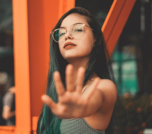 a woman with long dark hair and glasses holds out her hand signifying STOP - how to say no to people - life coaching for conscious living