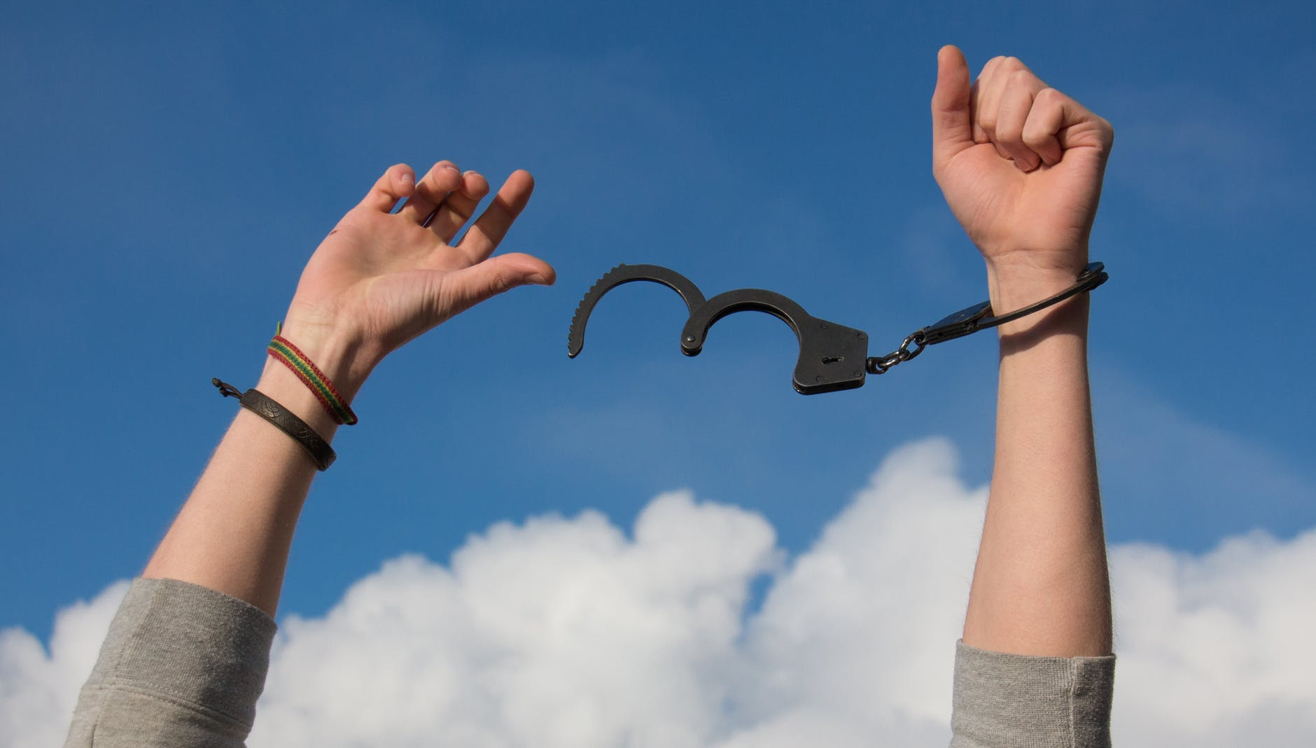 a mans arms break free of black handcuffs against a blue sky with fluffy white clouds - how to say no assertively - life coach - awakened living