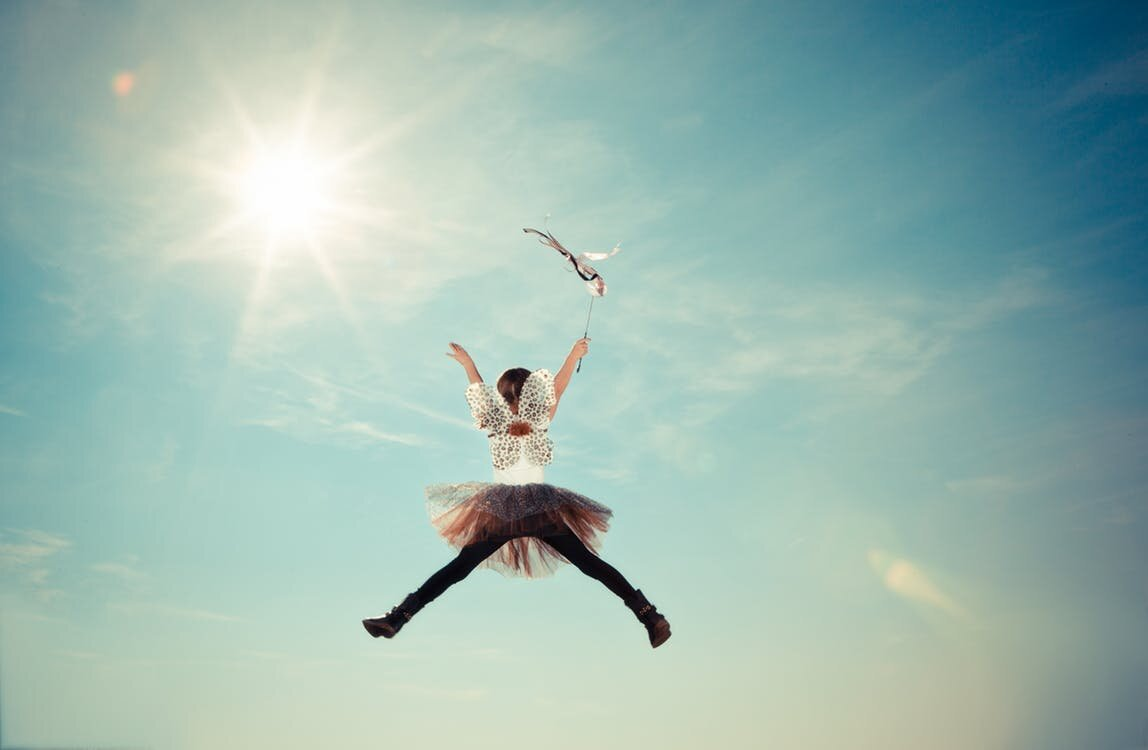 a woman in wings and tutu jumps for joy in a sunny sky