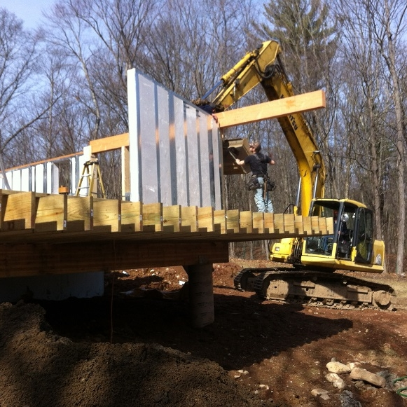 on-site excavator aids in placing a large beam