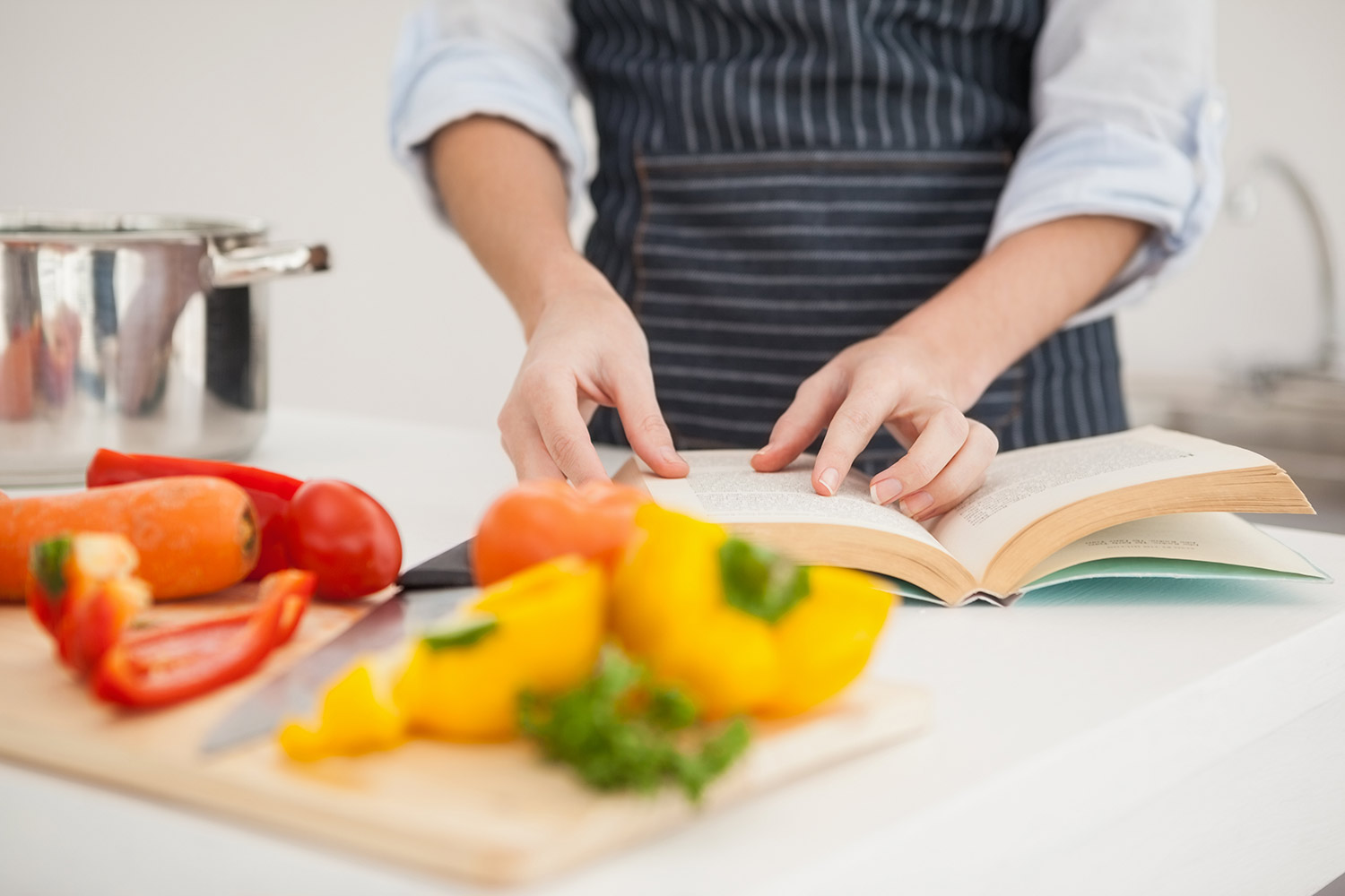 woman cooking with recipe book