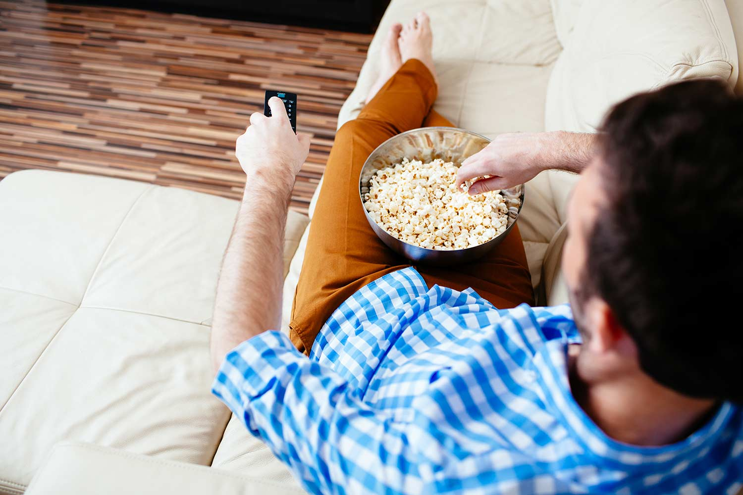 man in front of television with popcorn