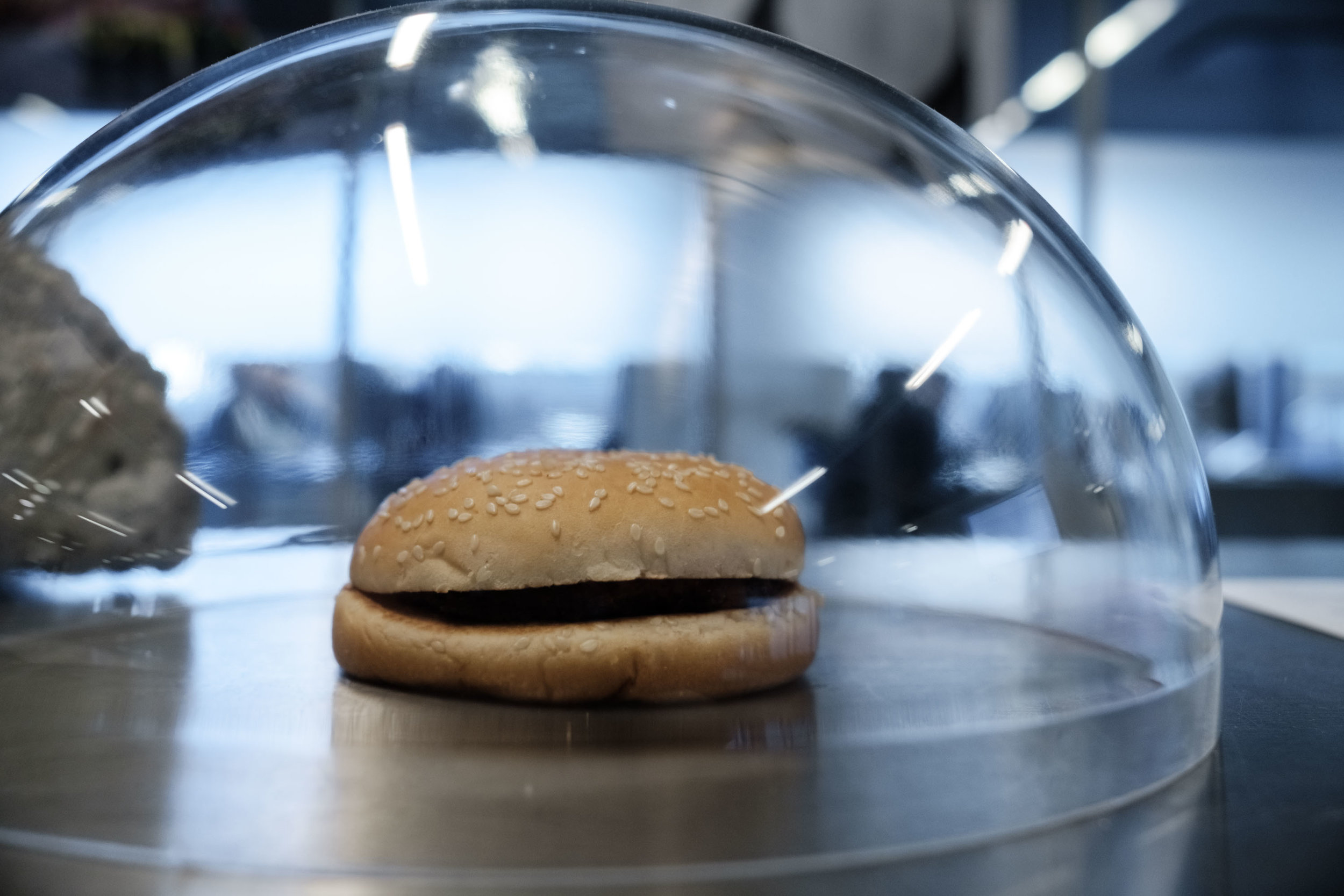 The fast-food hamburger   It was the epitome of the 'energy glut': fast, cheap & delicious. As critique grew of industrial meat, the slice of protein shifted, first to plants & legumes, then to in vitro meat. But there was no saving it, displayed before you is the last fast-food burger ever served in 2038. People still put slices of protein between buns - but golden arches and burger royalties are no more.  Preserved and donated by Tobias Linné