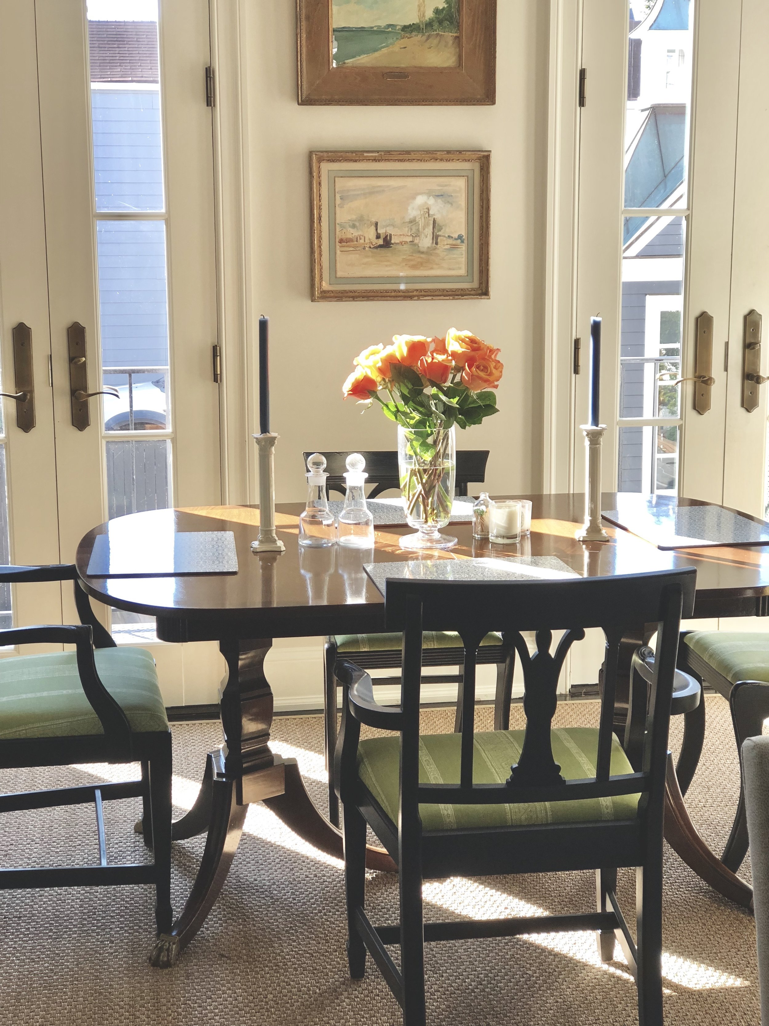 """This is where I'm writing you from — old chairs that I painted black, recovered in Carolina Irving """"Patmos Stripe,"""" easy seagrass rug, some Irish crystal….all in all, a happy spot."""