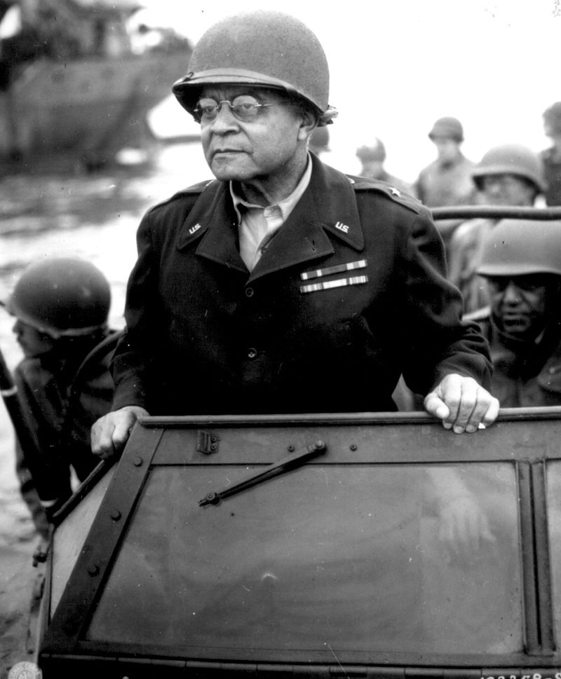 Brigadier General Benjamin O. Davis Sr. standing in a vehicle overseeing operations in France on the 8th August 1944