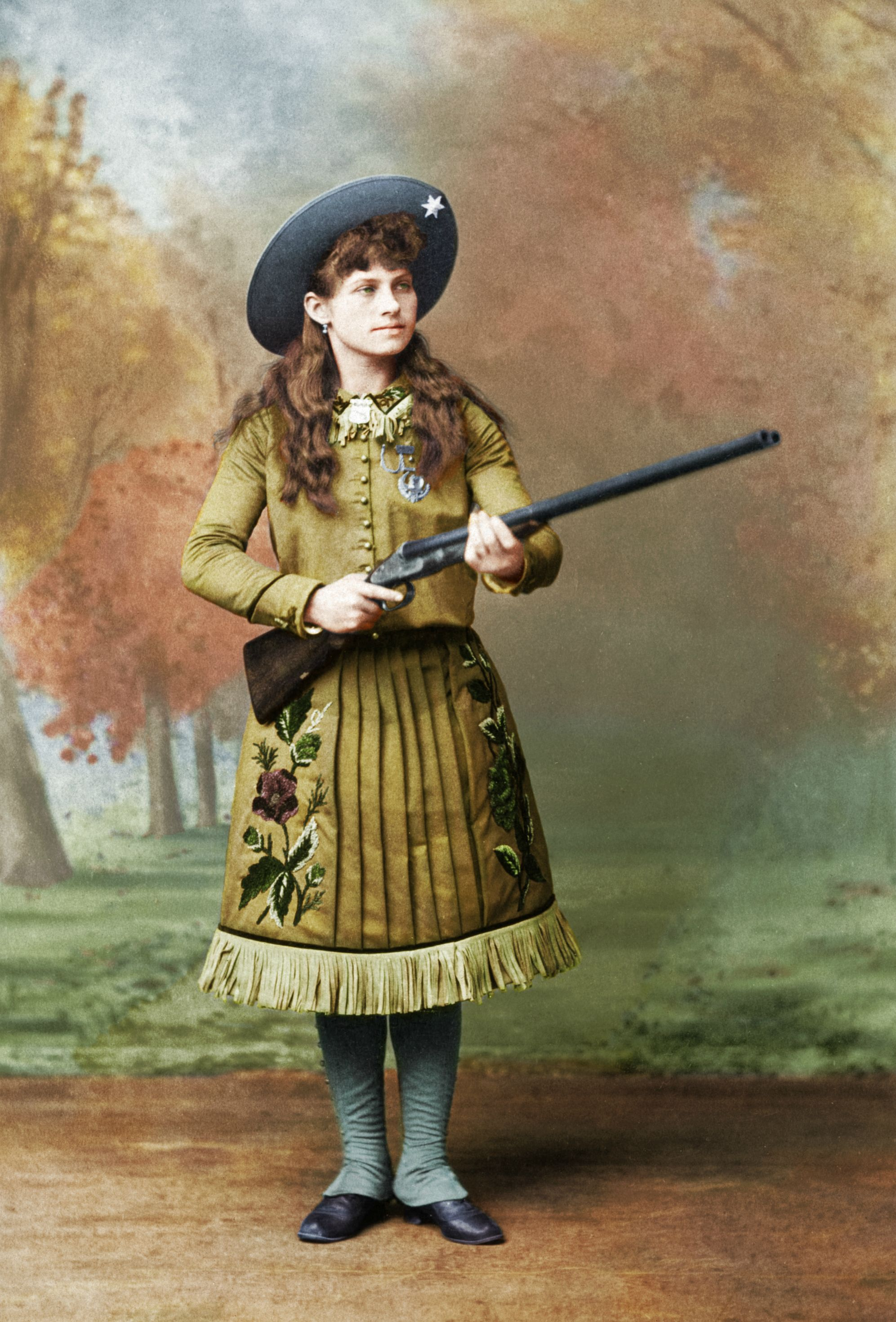 A photograph of Annie Oakley posing with one of her guns in 1888. Colorization by  Geebix