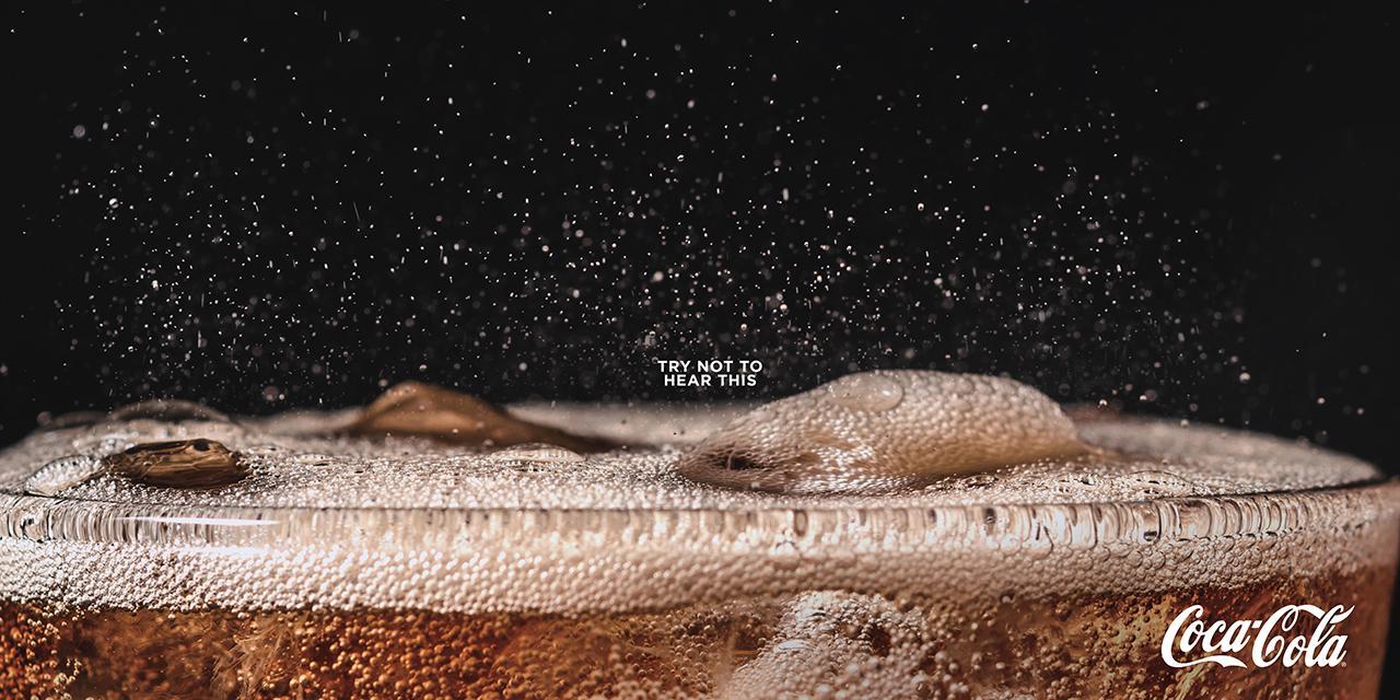 Exemplo de sinestesia. Anúncio impresso da Coca-Cola com bolhas efervescentes. Por DAVID The Agency. Disponível em <www.forbes.com/sites/willburns/2019/04/26/listen-to-these-new-print-ads-from-coca-cola/>. Acesso em 28 abr 2019.