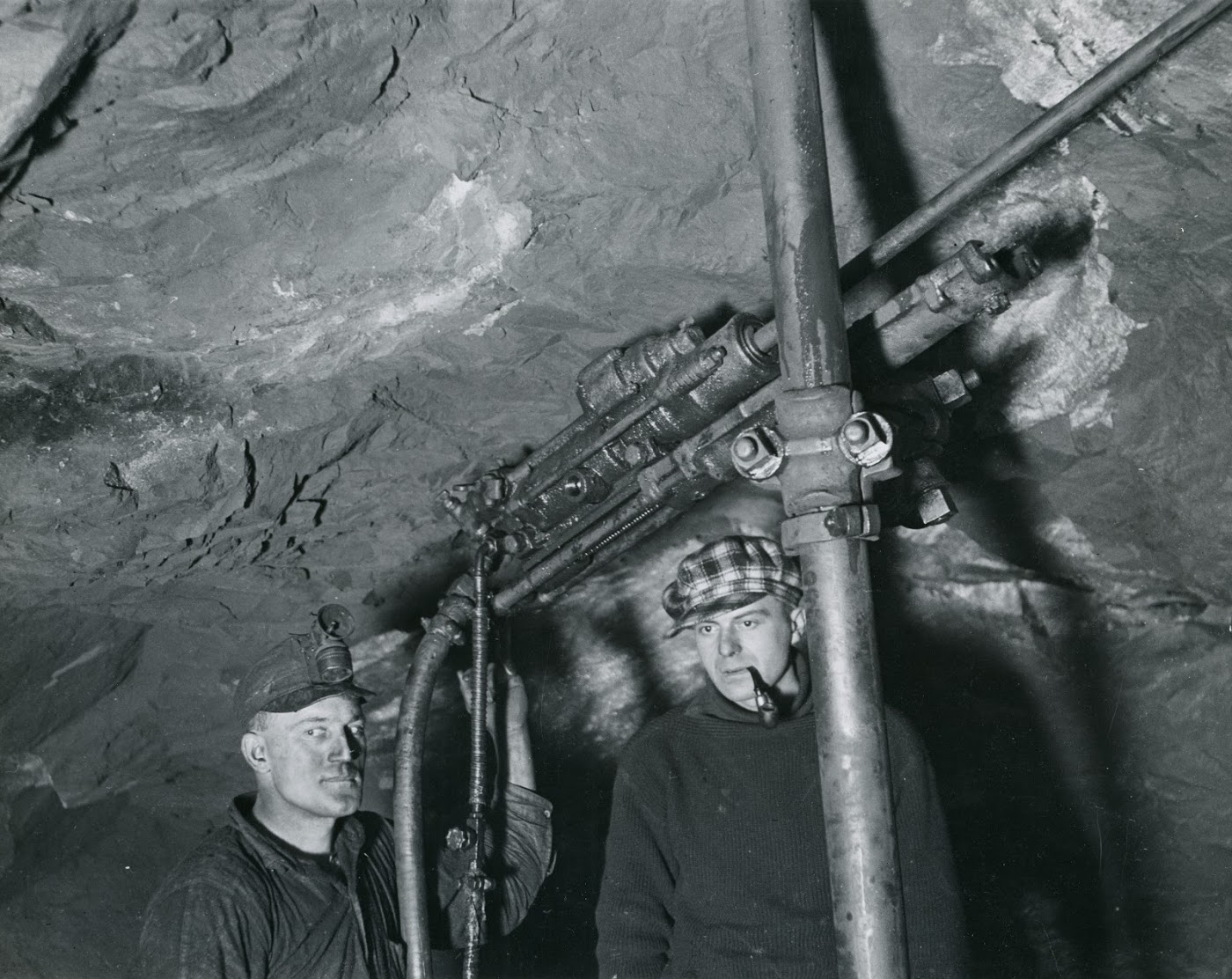 Photo 2309.0046: Two men in an unnamed mine, operating an early drill.