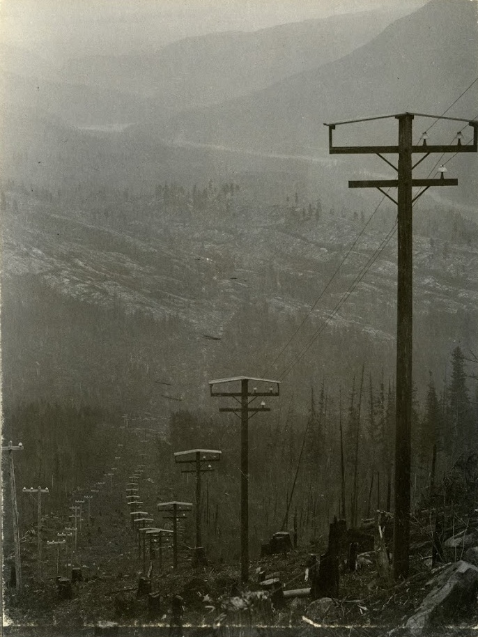 Photo 2348.0048: The first powerlines connecting the Bonnington Plant to Rossland, circa 1898. The roofs seen on top of the lines were specially created for the poles on the Bonnington - Rossland route, as engineers worries the heavy snow loads of the area would interrupt the electrical current if sitting directly on top of the insulators.