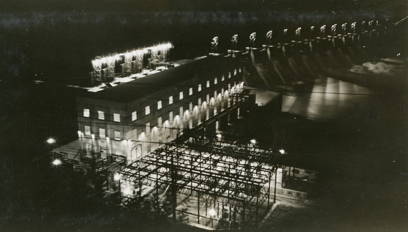 1932:Plant No. 4 is Built - With ever-expanding CM&S Operations, a fourth Dam is built upstream from the Bonnington operations on the Kootenay River, named Corra Linn. This plant includes 14 flow gates, which allow for increased and controlled water storage in the Kootenay Lake. This allows energy production to become fixed as opposed to the previous operating style in which electricity production was dependent on the natural flow of the river.Photo 2341.0111: Plant No. 4, or Corra Linn Dam, in operation in August 1932.