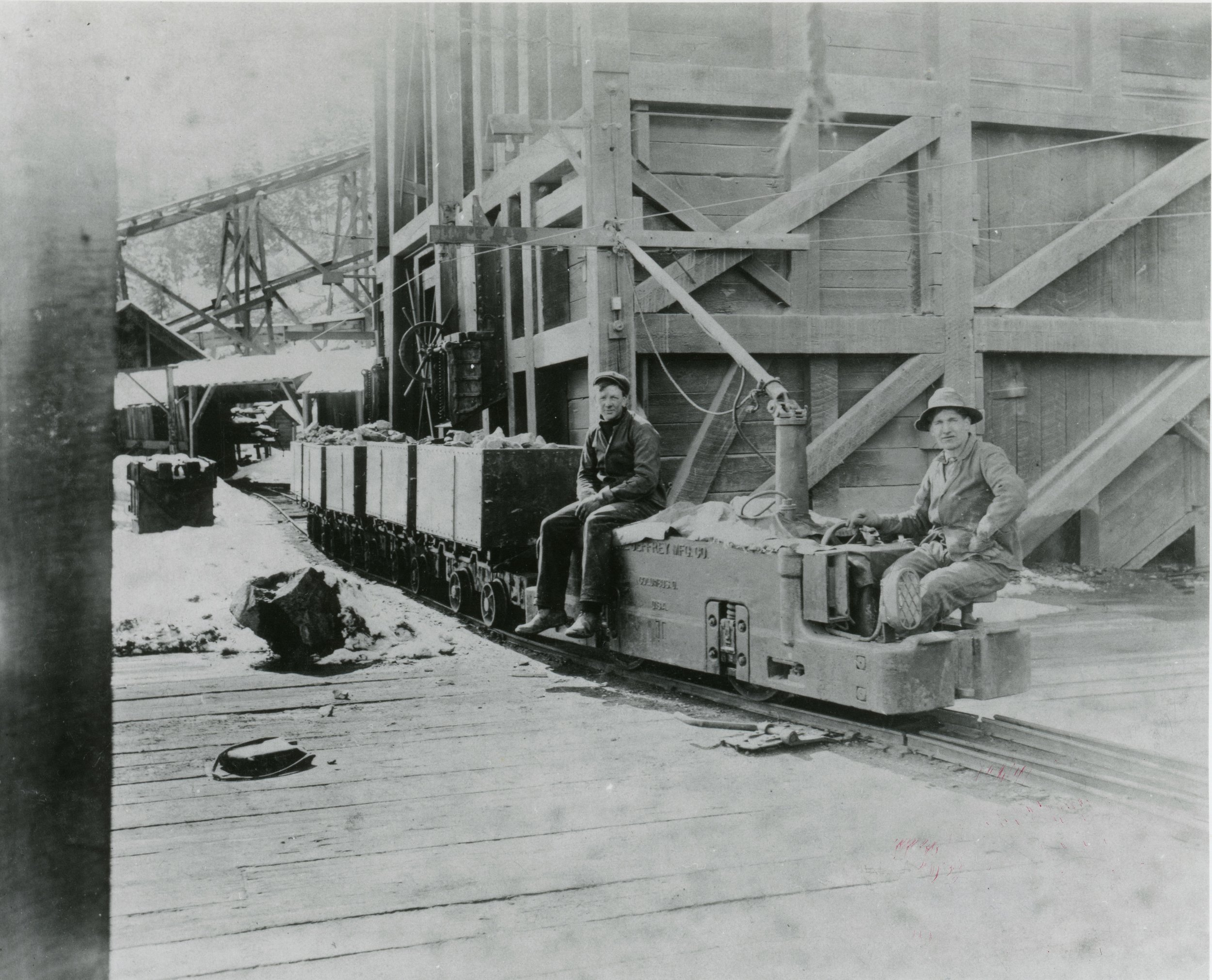 Photo 2304.0069: One of the electric trams used in the Centre Star Mine. As seen here, the small electric-run locomotives were able to haul many full ore cars at once. Date and names unknown.