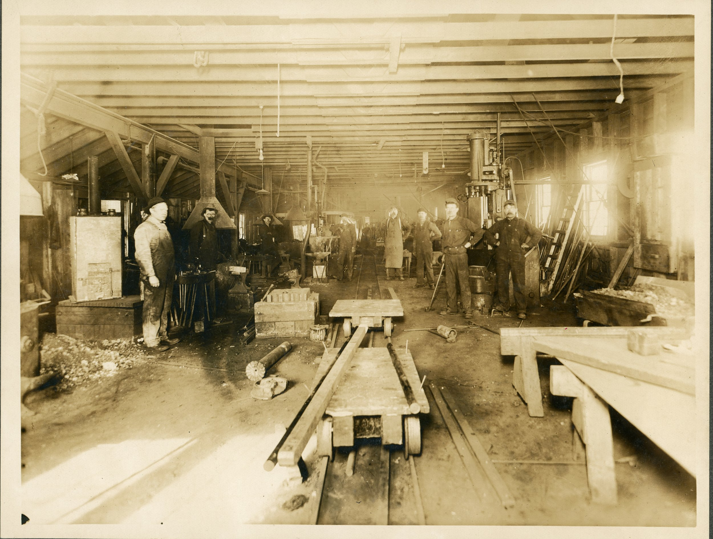 Photo 2304.0084: Blacksmith shop were a flatbed cart can be seen in the centre foreground and was most likely used to carry equipment in and out of the blacksmith shop. Far left: William Scholermer. Date unknown.