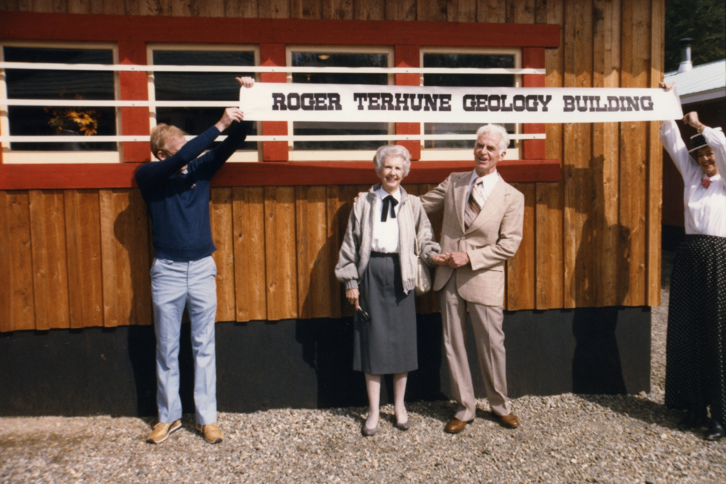Photo 2349.0096: The opening of the Roger Terhune Geology Building in September 1985 during Rossland's Golden City Days celebrations. Pictured from left to right: Brian Fulsom, Mrs. Terhune, and Roger Terhune.