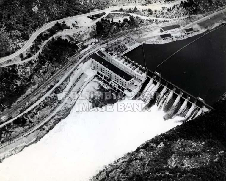 1944:Plant No. 5 is Built - Built to meet CM&S's power needs brought by the Second World War, a fifth power plant is built at the mouth of the Kootenay River. This plant is named the Brilliant Dam.Photo 2306.0057: The Brilliant Dam in operation, taken May 20th, 1951.