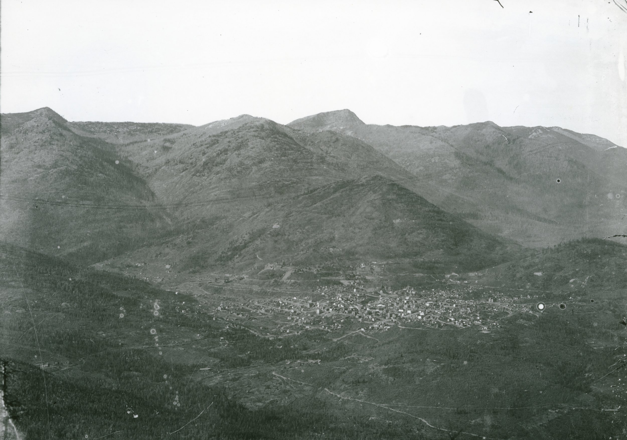 Photo 2311.0072: View of Rossland looking over the city from the south, circa 1902. Note the lack of trees on the surrounding mountains from the extensive logging operations.