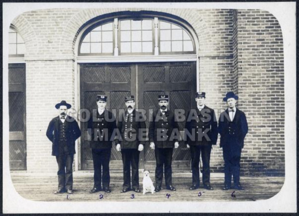 Photo 2276.0028: Rossland Firemen stand outside the Fire Hall, circa 1902. Numbered on the photo from left to right: 1: Paddy Walsh, 2: Frank Boyd, 3: Chief Donald Guthrie, 4: Joe Mattin, 5: Dan McDonald, 6: ? Templeman.