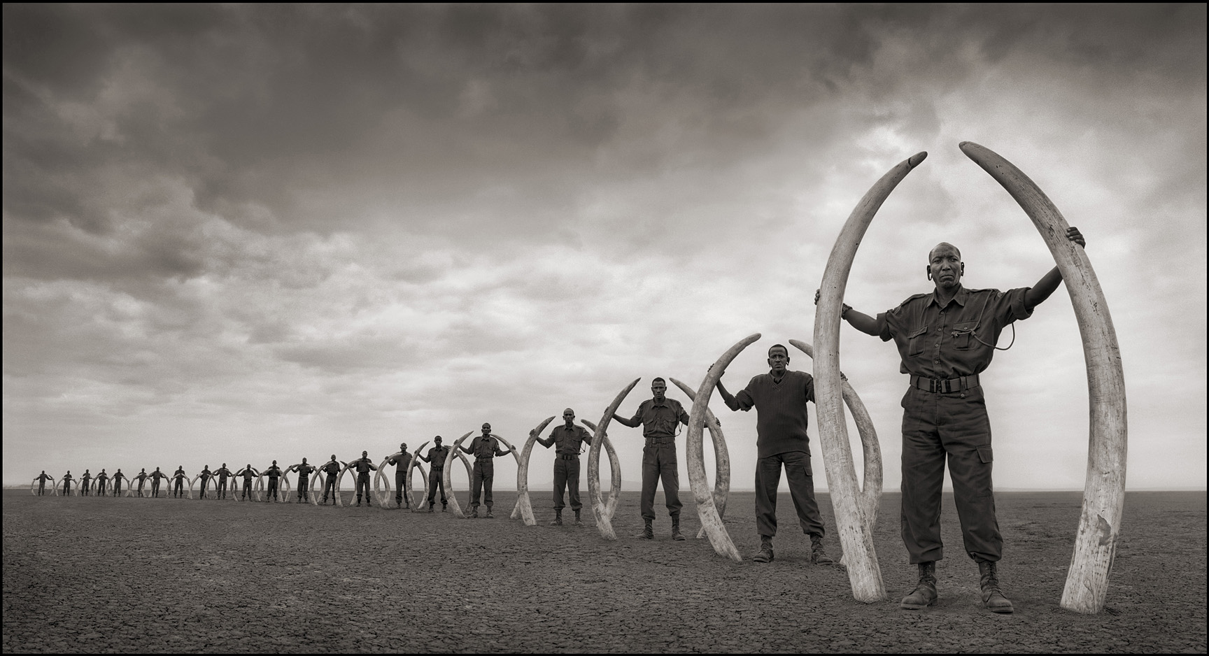 Line of Rangers with Tusks of Killed Elephants
