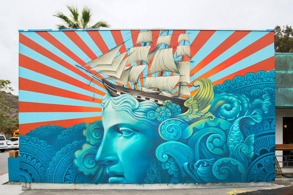 """Murals Remake a Hidden Streetscape   An often overlooked commercial strip in Laguna Beach's art festival district in Laguna Canyon is getting a makeover, with swaths of color beginning to dapple the sides of buildings to kick off what organizers are calling the Summer of Color. The blooming murals represent a new chapter for the 805-856 Laguna Canyon Road property, formerly known as the Festival Center but recently rebranded as The Hive. The 20,000-square-foot property, previously owned by resident and recently acquired by resident Mo Honarkar, was originally constructed in the late 1960s and was developed by Gary Sauter about 20 years ago.  Mark Orgill said Honarkar appreciated his vision for a vibrant contribution to the arts district and offered to partner with him to make it a reality. """"Originally what was envisioned was pretty vague; it was supposed to just be a platform to accommodate all things creative,"""" Orgill said. """"But now it's just going to kind of morph and grow organically."""" Currently, the commercial center is home to eight local businesses, with room for 12. Tenants include Kitchen in the Canyon, a satellite location for Laguna College of Art and Design's virtual reality department, and Laguna Beach Beer Company, which anticipates opening late this month . ..  READ MORE"""