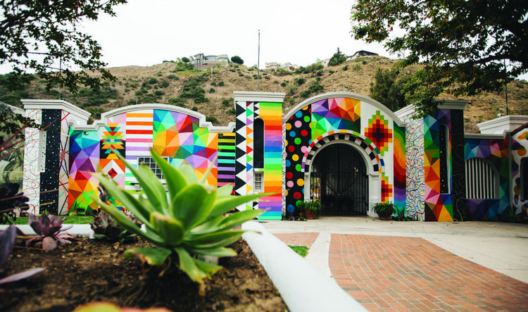 """Summer of Color Makes Big Splash In Arts Minded Beach Town     The village of Laguna Beach, with over 100 art galleries and studios and world renowned arts festivals, has drawn art lovers from all over the world to its picturesque seven mile coastline. Now art lovers have one more reason to come to Laguna: To view its newest art exhibit labeled """"Summer of Color.""""  This eye-catching, vibrantly hued collection of murals painted on the facade of a cluster of buildings along Laguna Canyon Road's Arts District, is the dream project of Mark Orgill, a designer and long-time resident of Laguna Beach who, along with his wife, Dora Wexell, developed and built [seven-degrees], a venue for unique, upscale corporate and private events.  Orgill and Wexell, are a couple deeply devoted and involved in the Laguna Beach art scene. Mark is president of Visit Laguna and Dora, president of First Thursdays Art Walk. You get the picture. When it comes to creating a vision for art, they care, do and share.  The buildings between 775 - 859 Laguna Canyon Road are, and will for the next five years be, canvasses for murals conceived and created by internationally recognized artists. The project was funded by local businessman Mo Honarkar, who bought [seven-degrees] last year and owns many neighboring properties, including the Art-A-Fair building.  READ MORE."""