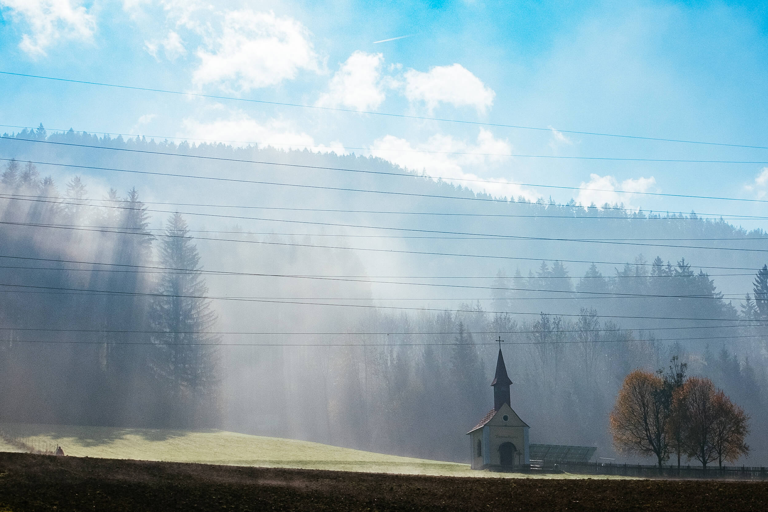 Small church lost in the morning fog on the roads of Carinthia