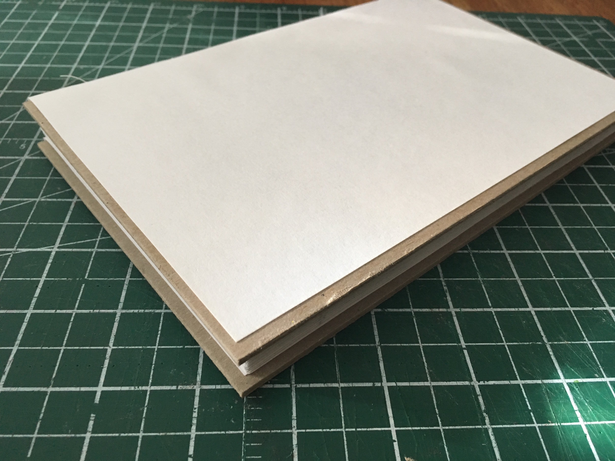 Step 3: - The boards are added, and the card stock is glued down over them. You can see the overhang here.