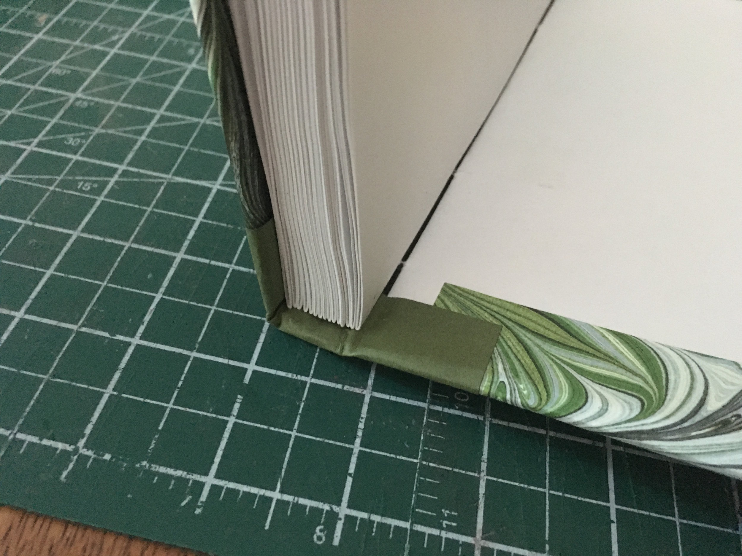 Step 9: - This is the tricky part. The card stock needs to be reasonably stiff so it'll hold up well, but it also needs to be flexible enough to allow it to be folded in and underneath the text block. I use my bookbinding awl to push it through. It's also risky because you might get glue on the text block. I got away with it this time, but in future I'll be sliding some wax paper around the text block to protect it first.