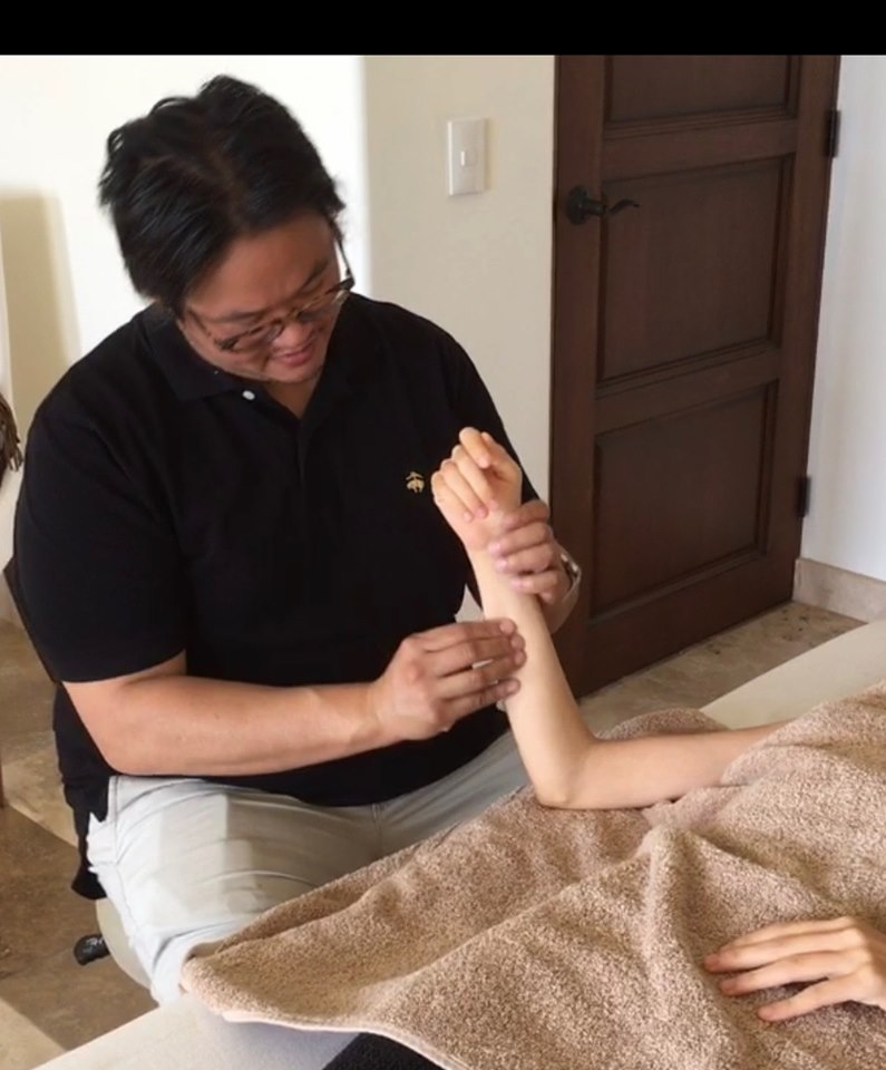 Dr. Shiu palpates her arm before needling.