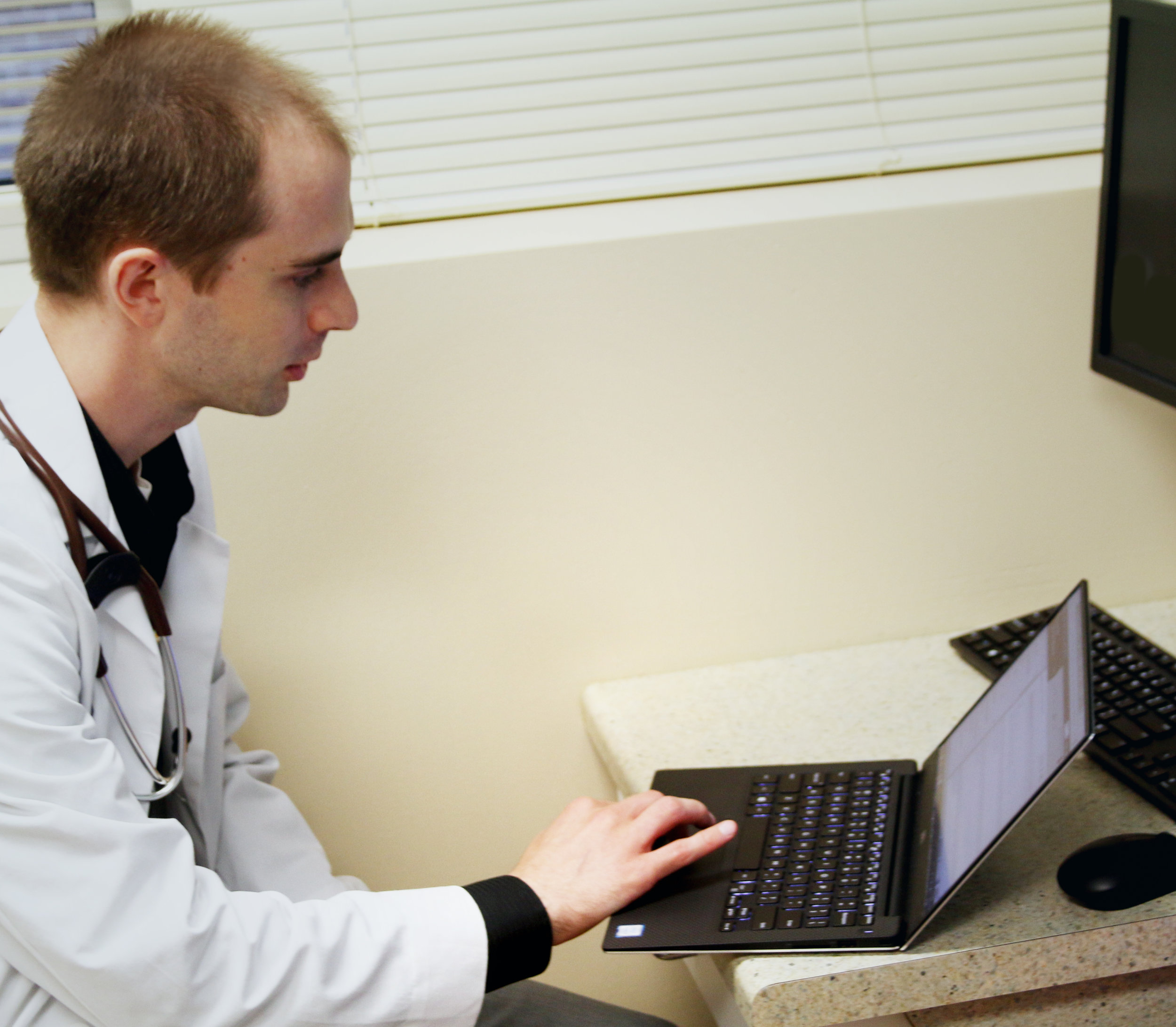 Doctor in white coat on laptop in front of desktop computer