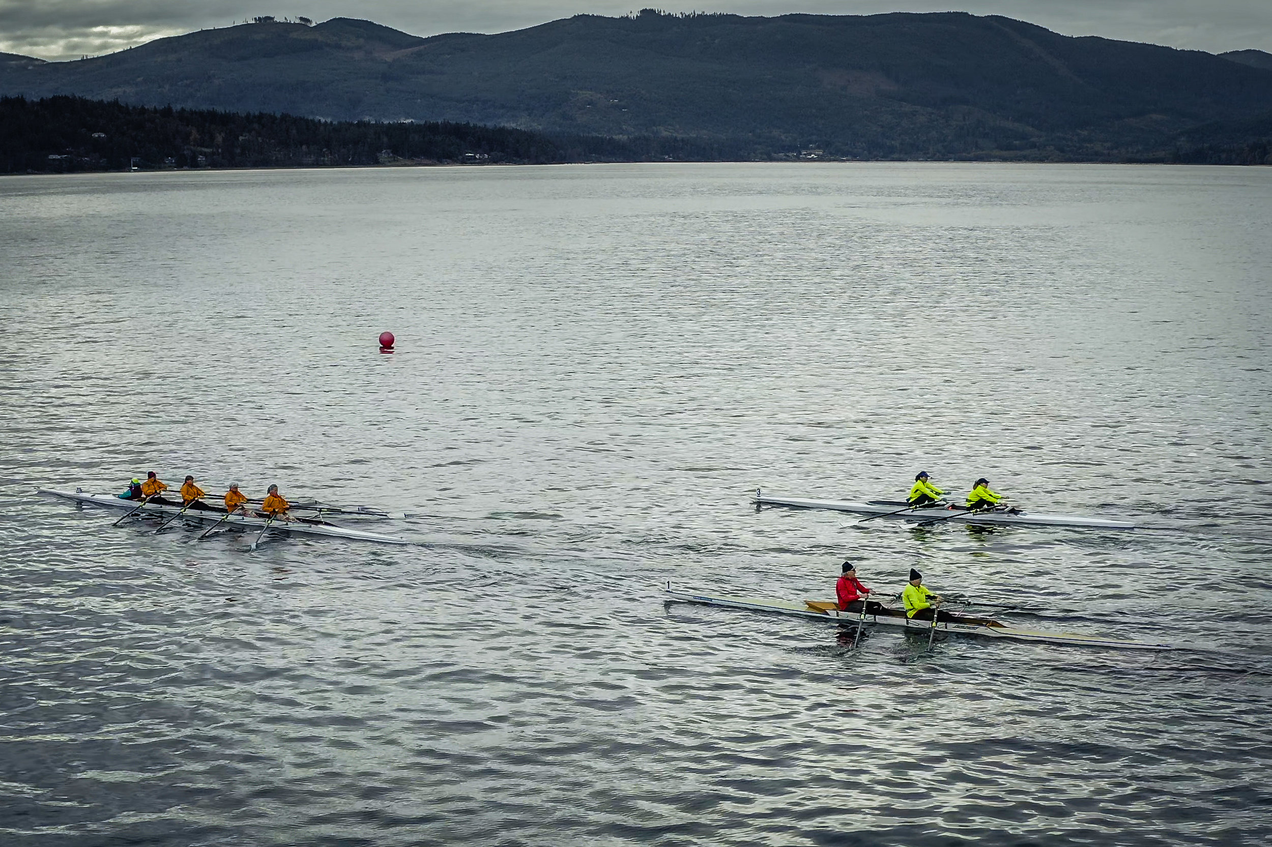 """Thirty-four rowers and paddlers in 18 craft from Sequim, Port Townsend and Port Angeles helped raise thousands of dollars for Volunteer Hospice of Clallam County in Sunday's (Sept. 29) race, the second half of Sequim Bay Yacht Club's Reach and Row for Hospice event. This was the 27th fundraiser, established as a sailing race in the 1990s and expanded in 2018 to include a rowing and paddling competition. Pictured from left, Tuf As Nails, a women's Port Townsend team, Two Old, Sequim and Port Townsend rowers (foreground) and Tennis Bracelet, a women's SBYC team, both from Sequim. Overall winners were Sandra Wanstall of Port Townsend, Alan Clark, Sequim, second; Charley Kanienski, Port Townsend, third; and Tuf As Nails, fourth. SBYC, which has raised more than $360,000 for VHOCC in the past quarter century, continues its fundraising through Dec. 31. Contributions can be sent directly to VHOCC, 829 East 8th Street, Port Angeles WA 98362 with """"Reach and Row for Hospice""""in the memo line of checks. Photo by Dave Pitman, Olympic Aerial Solutions"""