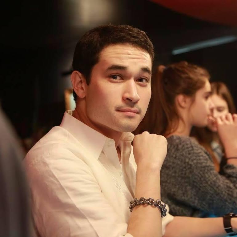 Mendez, sitting at the bar in a barong tagalog, smiles at the camera.