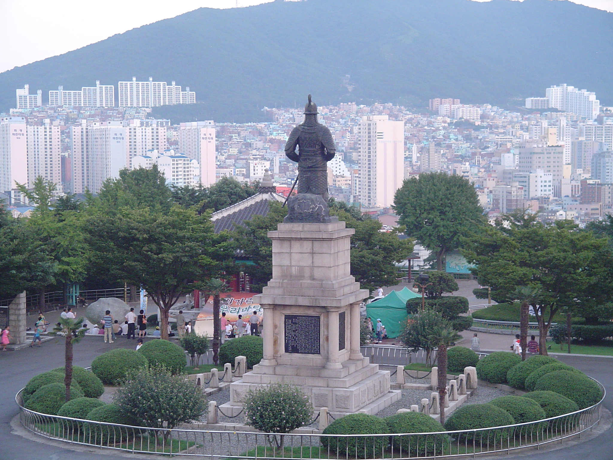 A statue of Admiral I Sunsin in a park atop Busan Tower looks out across the city by day. Photo by Jeff Harr,  CC BY-SA 3.0 .