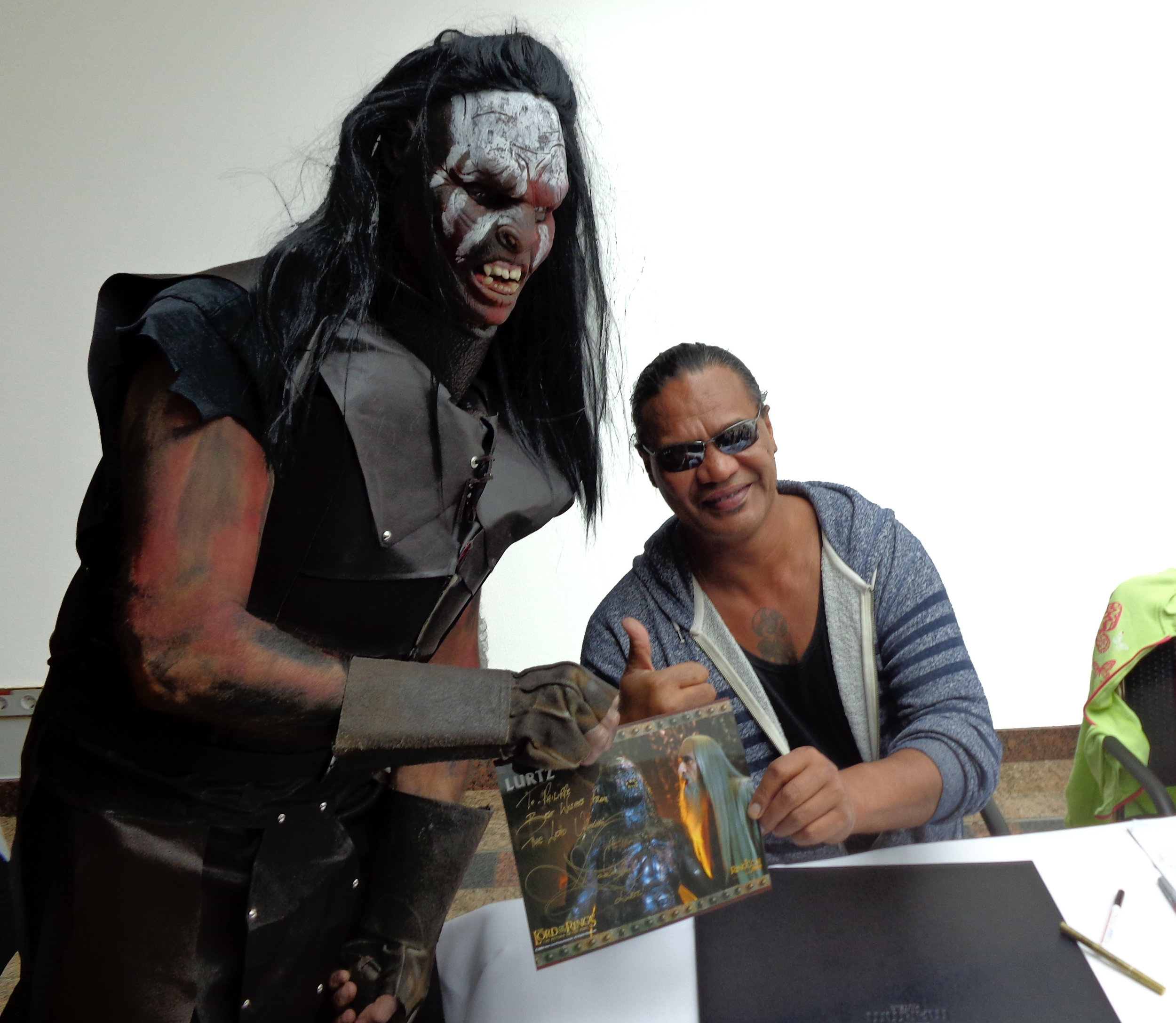 Well, this is mildly awkward now. From Wikimedia Commons, a fan cosplaying as Lurtz the orc from  The Fellowship of the Ring  film adaptation poses with an autographed picture and a cheerful Lawrence Makoare, the Māori actor who played that character.