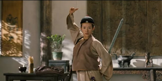 Zhāng Zìyí in men's clothing posing badassfully with her sword in that restaurant fight scene from  Crouching Tiger, Hidden Dragon.