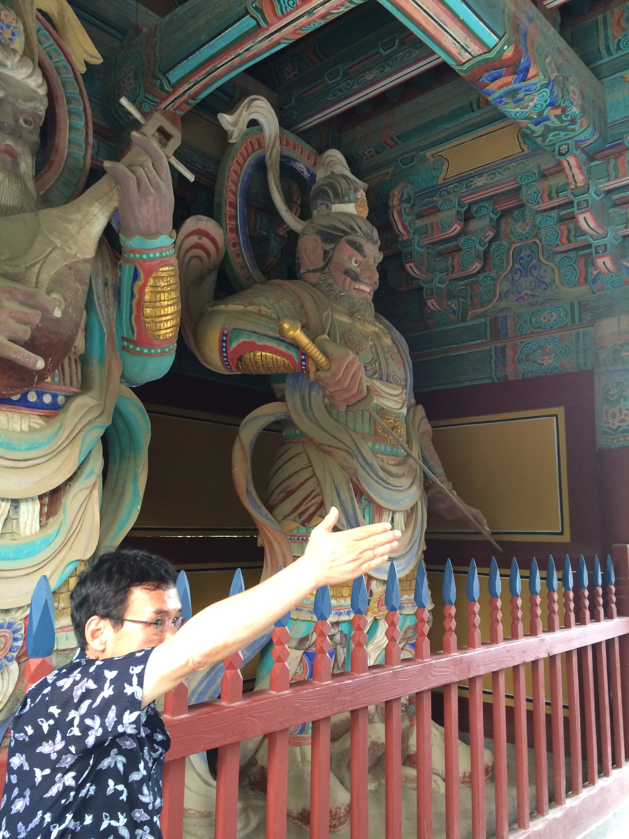 Tour guide Sam Gim stands before towering, colorful statues of guardian gods in a Korean Buddhist temple. Dhṛtarāṣṭra/Jiguk's on the left playing his lute, Virūḍhaka/Jeungjang brandishing his sword on the right.